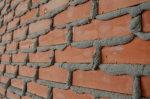 Vue à l'horizontale, le ciment qui traverse les briques rouges symbolise les anciennes clôtures qui emprisonnaient les prisonniers anti-communistes. Quant aux débordements verticaux du ciment, ils symbolisent les larmes des persécutés. (c) Pétronille TOFIDJI